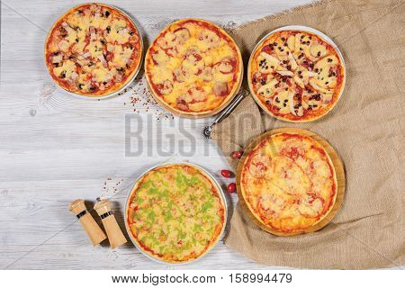 Pizza variety served on wooden board and background, from above and blank space