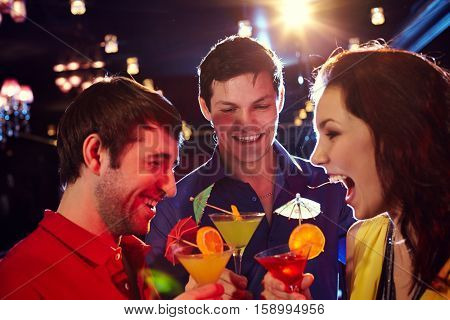 happy company shouting in the club with drinks