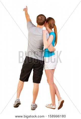Back view of young couple pointing at wall (woman and man). newlyweds on their honeymoon. Rear view people collection.   backside view of person.  Isolated over white background.