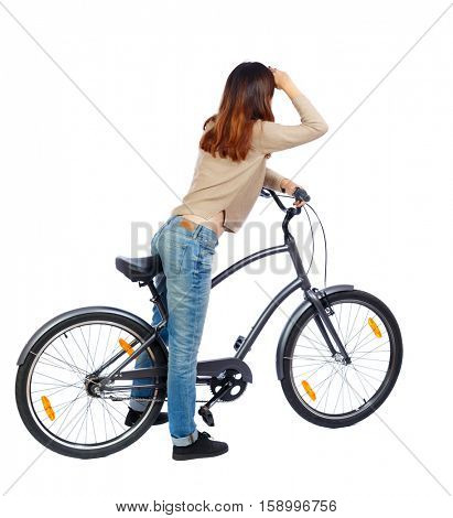 back side view woman with a bicycle. cyclist sits on bike. Rear view people collection. backside view person. Isolated over white background Girl on bike put her hand to her eyes staring into distance