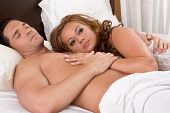 stock photo of seminude  - Young sexy naked heterosexual couple love in bed - JPG
