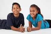 pic of ten years old  - cheerful boy and girl relaxing on the floor on a white background - JPG