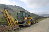stock photo of jcb  - A mechanical digger parked in remote highland glen - JPG