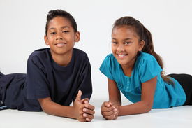 stock photo of ten years old  - cheerful boy and girl relaxing on the floor on a white background - JPG