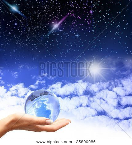 Globe in human hand against blue sky and stars in cosmos. Environmental protection concept.