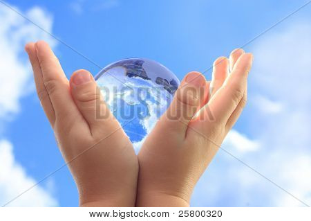 Globe in child hands against blue sky.