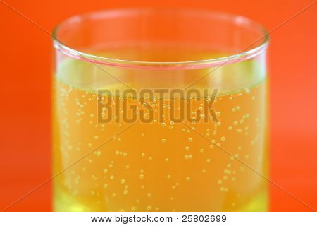 A glass of orange flavored calcium effervescent tablet dissolving in water