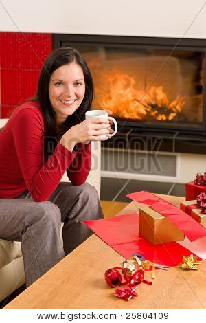 Happy woman wrapping Christmas present by fireplace enjoying hot drink