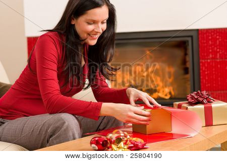 Happy woman in red wrapping Christmas present by home fireplace