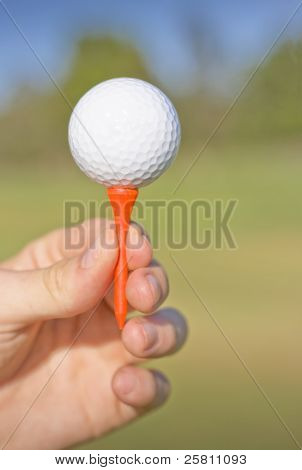 Hand Holding Golf Ball And Tee