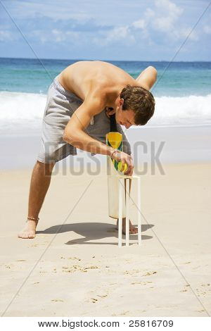 Man Playing Beach Cricket