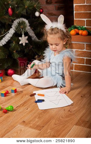 Little girl drawing near Christmas tree