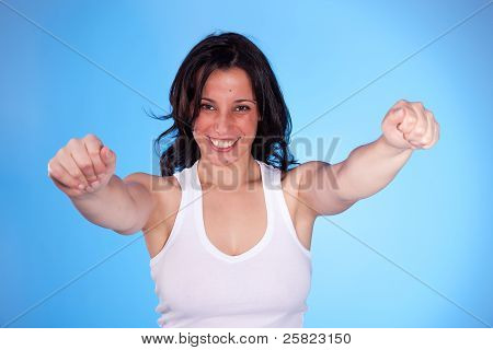 Beautiful  Woman With Arms Raised As Victory Signal, Isolated On Blue. Studio Shot