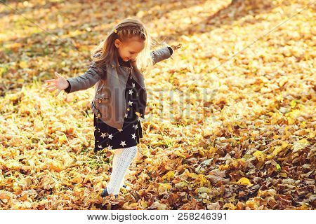 poster of Happy Child Walking In Autumn Park. Baby Girl Throwing The Fallen Leaves Up. Beautiful Golden Autumn