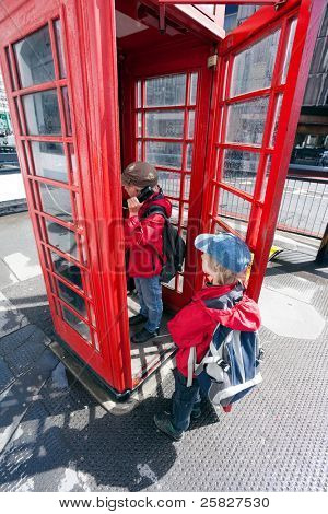 Boy talking in traditional red London pay phone box