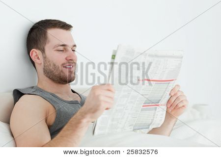 Attractive man reading a newspaper in his bedroom