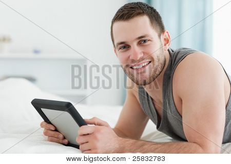 Happy man using a tablet computer while lying on his belly in his bedroom