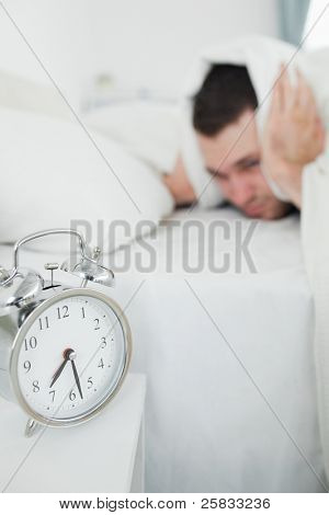 Portrait of a exhausted man covering his ears while his alarm clock is ringing in his bedroom