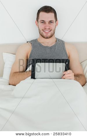 Portrait of a happy man using a tablet computer in his bedroom
