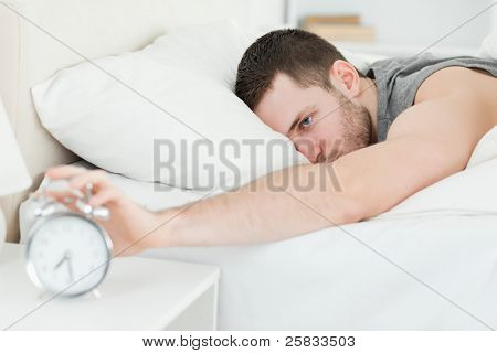 Handsome man being awakened by an alarm clock in his bedroom