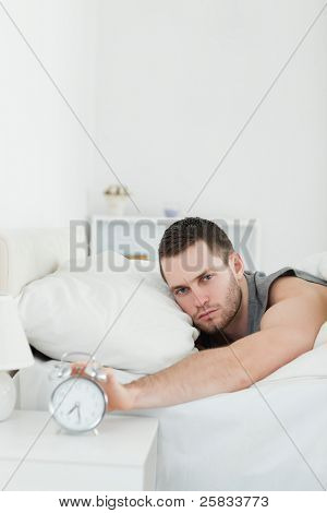 Portrait of a handsome man being awakened by an alarm clock in his bedroom