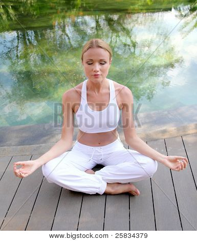 Woman doing yoga exercises on pool deck