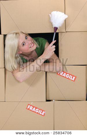 radiante rubia en medio de cajas de cartón con plumero
