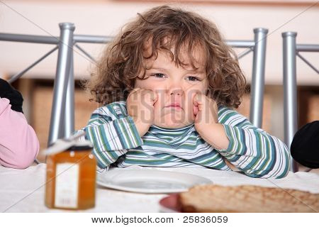little boy grouching in front a plate of crepes