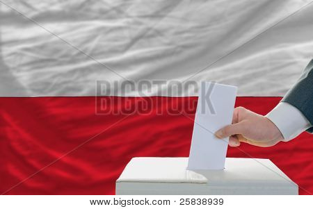 Man Voting On Elections In Poland In Front Of Flag