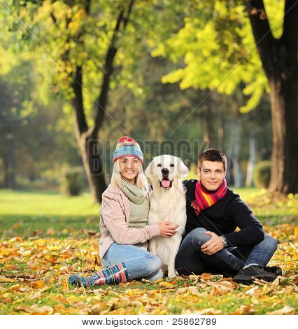 Smiling young man and woman hugging a labrador retreiver dog out in the park