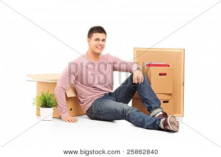Smiling man resting from moving into a new home with many boxes around him