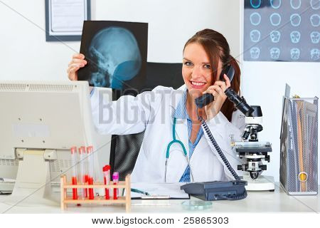 Smiling Female Medical Doctor Speaking Phone And Holding Patients Roentgen