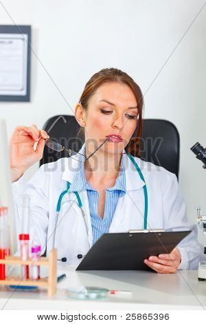 Thoughtful Female Medical Doctor Looking In Clipboard At Cabinet