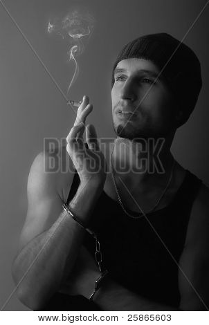 Bad Man In Handcuffs With A Cigarette