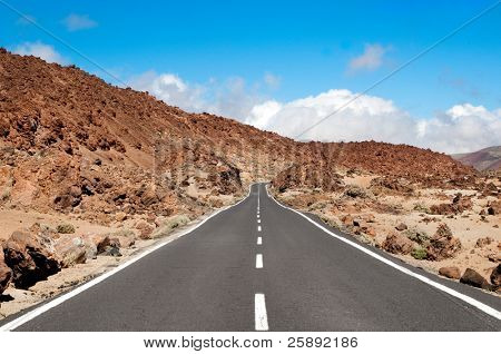 Empty road crossing an arid mountain, Lanzarote, Canary islands, Spain