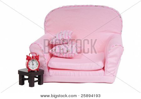 Comfortable pink armchair with alarm-clock on the table, isolated