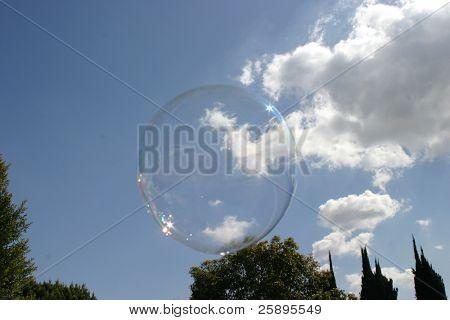 a soap bubble gently floats to earth showing white fluffy clouds and blue sky through its transparent air filled membrane