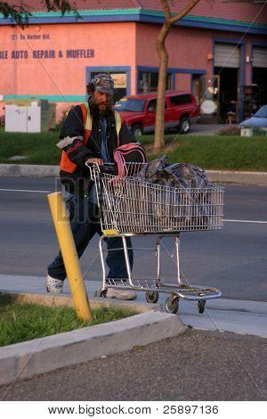 ein Obdachloser mit einem Warenkorb legen voll von seinem Nachlass, anzeigen erster hand die Notlage der