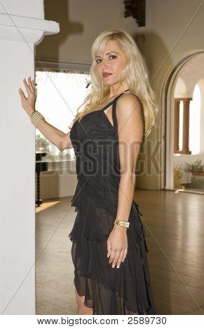 Beautiful Blond Standing Next To A Pillar