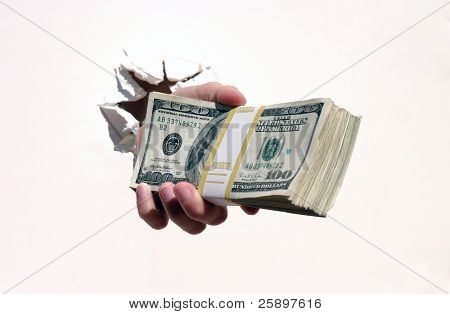 a pile o cash, a human hand crashes through an isolated white wall while holding a pile of money.