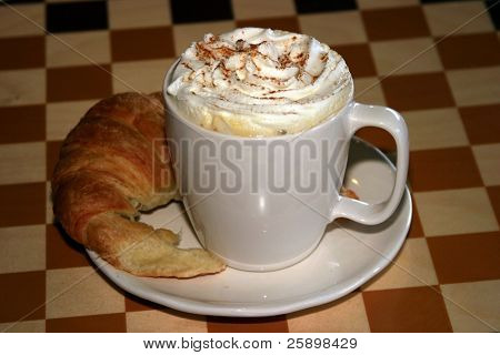 Latte with croissant  and whipped cream and chocolate power