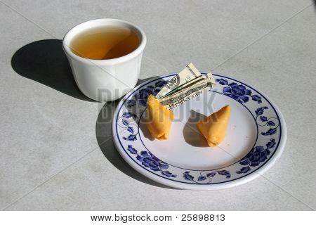 Fortune cookie with $100.00 dollar bill sticing out of it with green tea