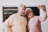 Old Couple Taking Photo In Airport In Waiting Room. Senior Person In Airport. Tourism Concept. Coupl poster