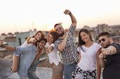 Group Of Young People Having Fun At A Summertime Rooftop Party, At Sunset. Focus On The Couple In Th poster