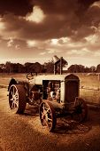 stock photo of yesteryear  - Turn The Crank And Take A Ride Down Memory Lane On A Agricultural Tractor From Yesteryear - JPG