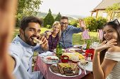 Group Of Friends Having A Backyard Barbecue Party, Having Fun Taking Selfies. Focus On The Couple In poster