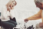Couple Of Old People Playing Chess At Home. Indoor Fun. Grandfather And Grandmother. People With Gra poster