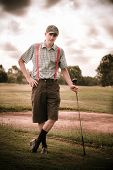 stock photo of olden days  - Happy Old Fashioned Golfer Leans On His Vintage Golf Stick In Front Of A Sand Bunker On A Golfing Fairway In An Olden Day Portait - JPG