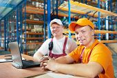 two young handsome workers man in uniform in front of warehouse rack arrangement stillages using not