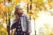 Cute Little Girl Playing In Autumn Park. Happy Child Playing With Fallen Leaves. Autumn Kids Fashion poster